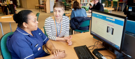 Librarian and nurse sit in front of computer inside library.