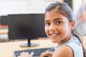 school girl with computer in classrom