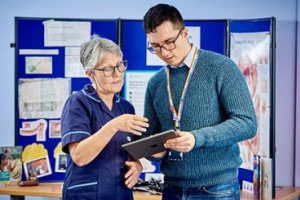 librarian talks to nurse in library setting