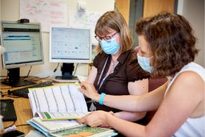 two colleagues work on paper and computer health information